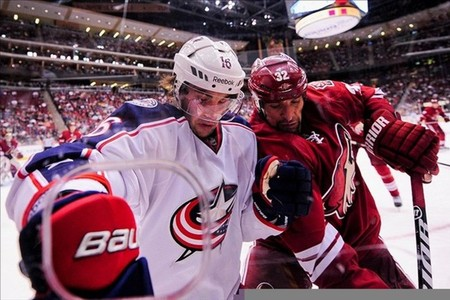 Mar. 3, 2012; Glendale, AZ, USA; Columbus Blue Jackets center Derick Brassard (16) and Phoenix Coyotes defenseman Michal Rozsival (32) battle for the puck along the boards during the third period at Jobing.com Arena. The Blue Jackets won 5-2.  Mandatory Credit: Matt Kartozian-US PRESSWIRE