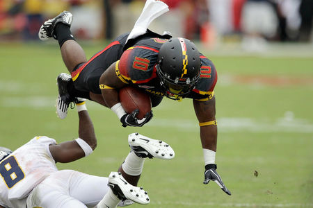 COLLEGE PARK, MD - SEPTEMBER 17: Running back D.J. Adams #10 of the Maryland Terrapins is tackled by defensive back Keith Tandy #8 of the West Virginia Mountaineers during the second half at Byrd Stadium on September 17, 2011 in College Park, Maryland. West Virginia defeated Maryland 37-31. (Photo by Rob Carr/Getty Images)