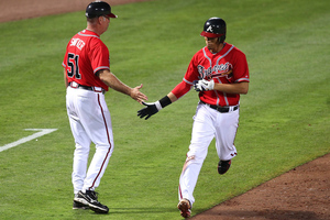 ATLANTA, GA - JUNE 15:  Shortstop Andrelton Simmons #19 of the Atlanta Braves is congratulated by third base coach Brian Snitker #51 during the game against the Baltimore Orioles at Turner Field on June 15, 2012 in Atlanta, Georgia.  (Photo by Mike Zarrilli/Getty Images)