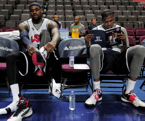 July 18, 2012; Manchester, UNITED KINGDOM; United States forward LeBron James (left) puts on his shoe as guard Kevin Durant (right) reads a game program during training for the 2012 London Olympic Games warm-up match against Great Britain at the Manchester Evening News Arena. Mandatory Credit: Joe Toth-US PRESSWIRE
