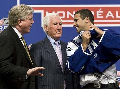 Nazem-kadri-laughs-with-brian-burke-left-and-cliff-fletcher-as-he-slips-on-a-leafs-jersey-june-26-2009